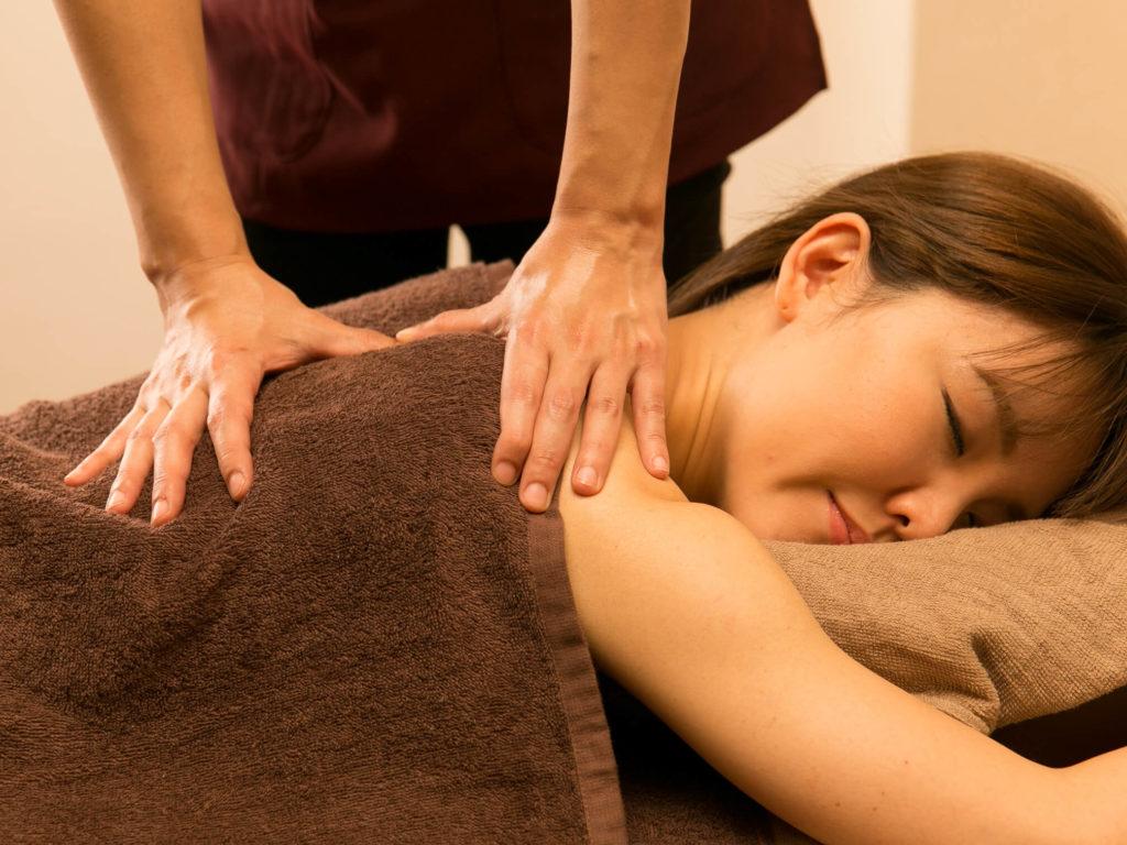 肩甲骨のマッサージを受ける女性